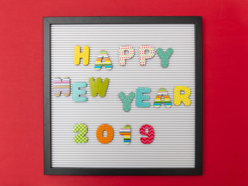Board with black frame, text happy new year 2019 in colorful letters, red wall background stock photos