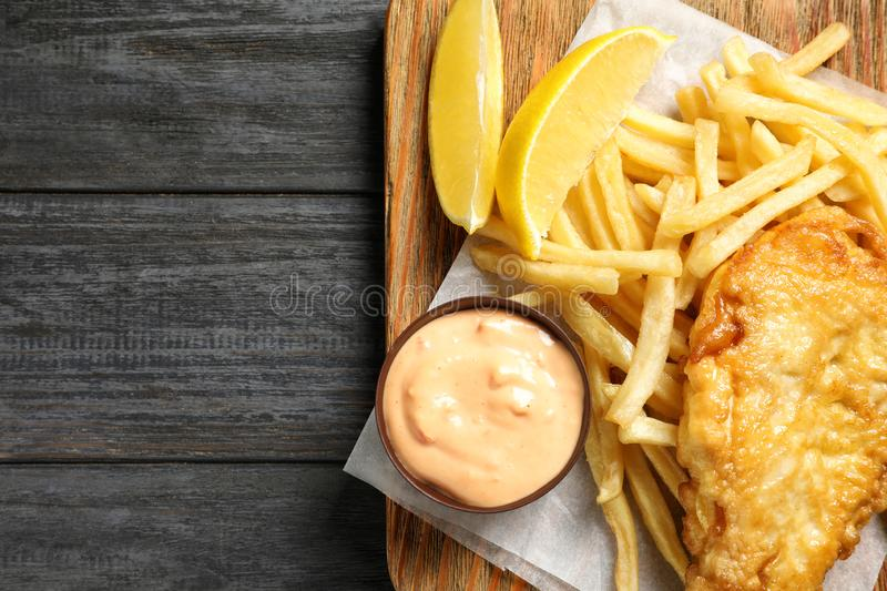 Board with British traditional fish and potato chips on wooden background, top view royalty free stock images