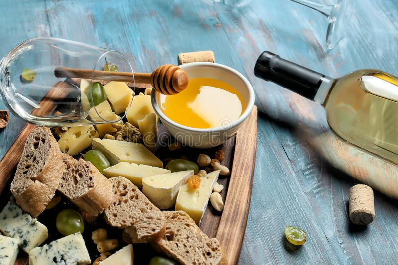 Board with cheese, honey and bottle of white wine on color wooden table royalty free stock images