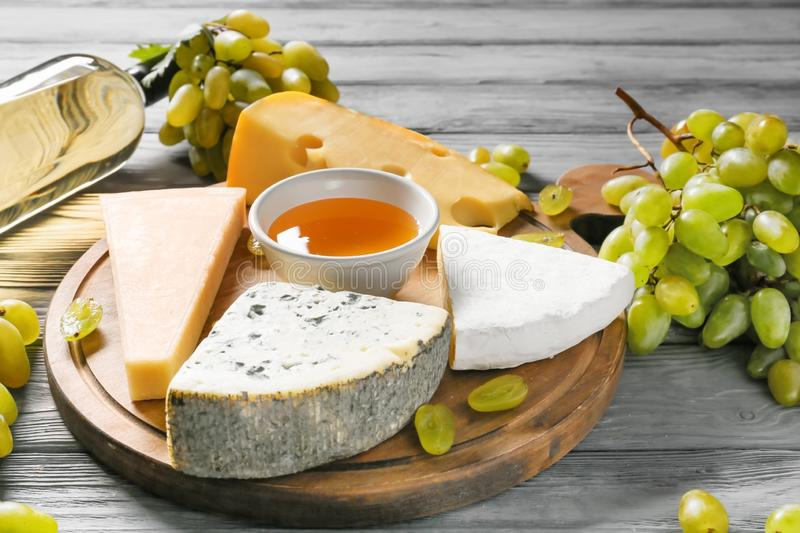 Board with cheese, ripe grapes and bottle of white wine on wooden table royalty free stock photo