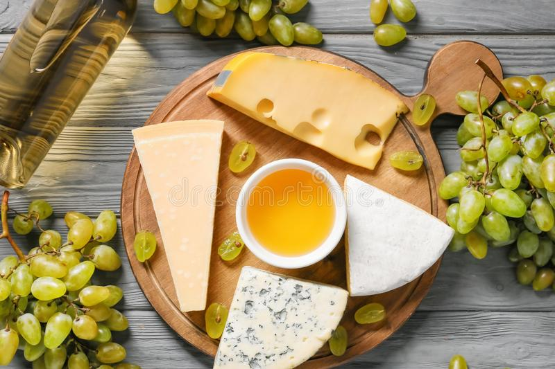 Board with cheese, ripe grapes and bottle of white wine on wooden table royalty free stock photos