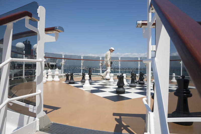 On-board chess. On board chess, passenger arranges the chess men in readiness for a game on board the cruise ship, Queen Elizabeth stock photo