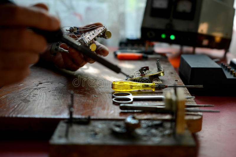 Board chip soldering. Yellow screwdriver on the table, the soldering iron is in the hands stock images
