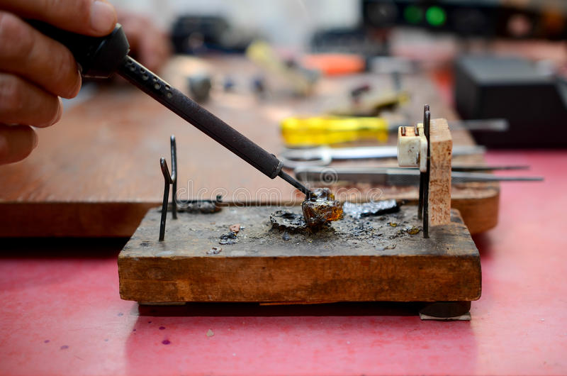 Board chip soldering. Yellow screwdriver on the table, the soldering iron is in the hands royalty free stock photo