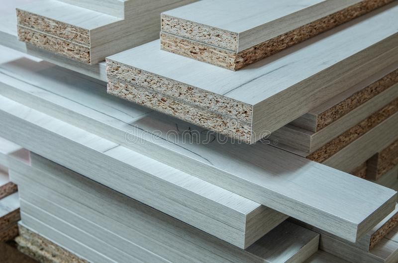 Board chipboard cut parts for furniture production close-up. Chipboard cut parts for the production and assembly of furniture, close-up royalty free stock photography