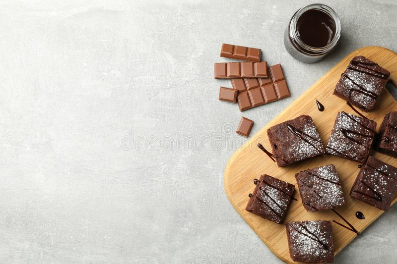 Board with chocolate cake slices and chocolate on grey background. Space for text royalty free stock photography