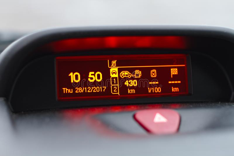 Digital lcd screen of a car. On board computer showing date and time, fuel consumption info and trip lenght in kilometers. Also hazard warning lights button stock photography