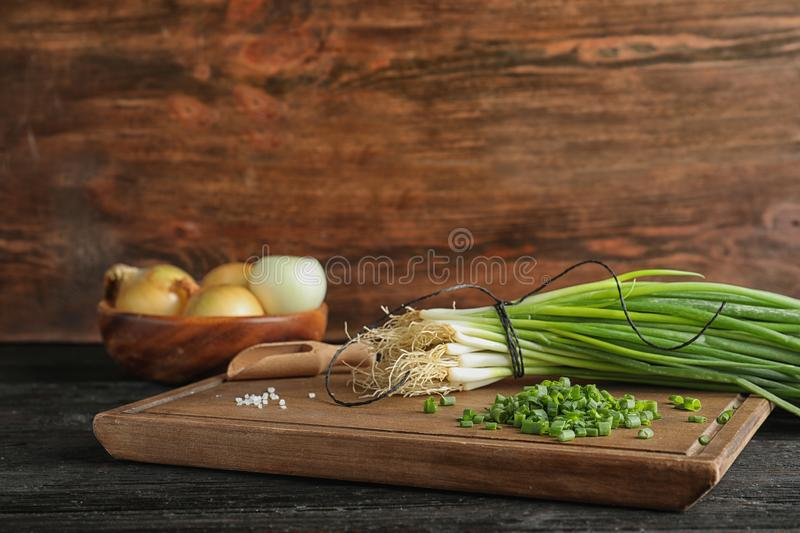 Board with cut green onion and salt on dark wooden table royalty free stock image