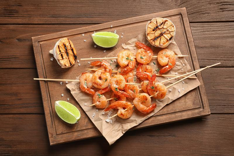 Board with delicious fried shrimp skewers, lime and garlic on wooden background, top view stock photography