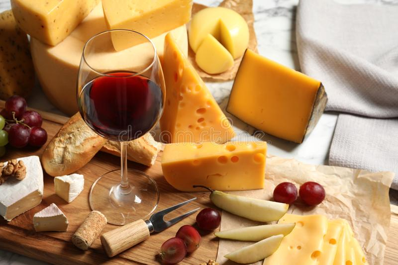 Board with different kinds of delicious cheese, snacks and wine. On marble table stock photos