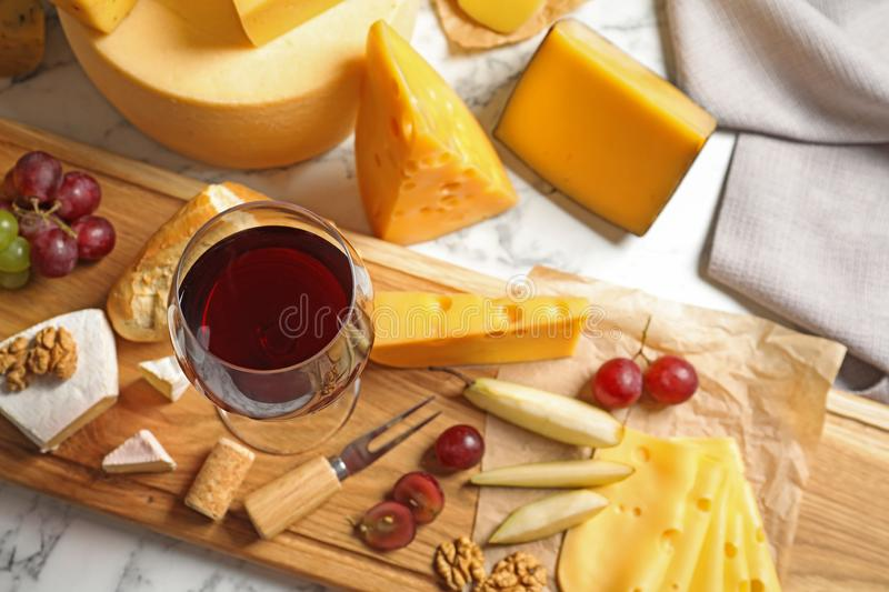 Board with different kinds of delicious cheese, snacks and wine. On marble table royalty free stock photos