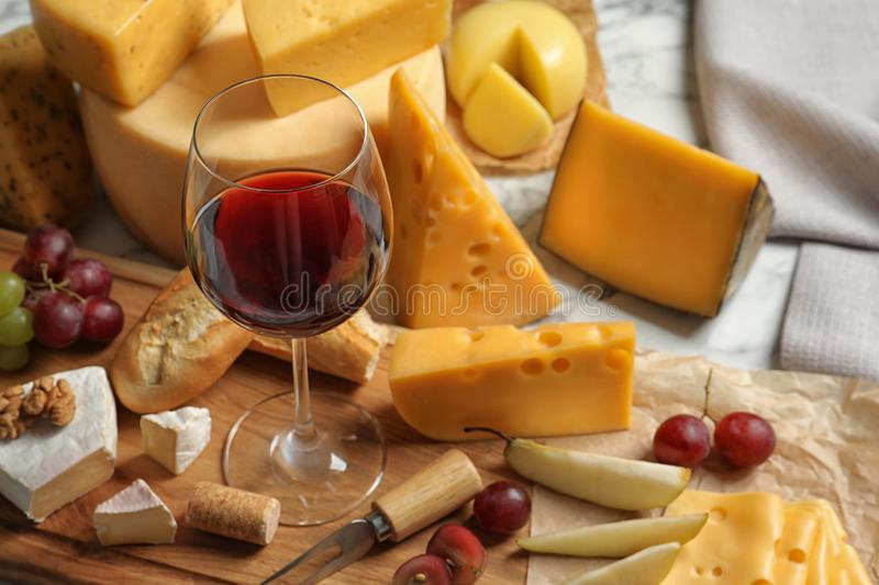 Board with different kinds of delicious cheese, snacks and wine. On marble table stock image