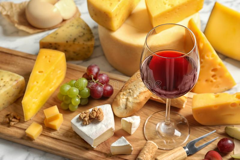 Board with different kinds of delicious cheese, snacks and wine on table. Board with different kinds of delicious cheese, snacks and wine on marble table stock photos