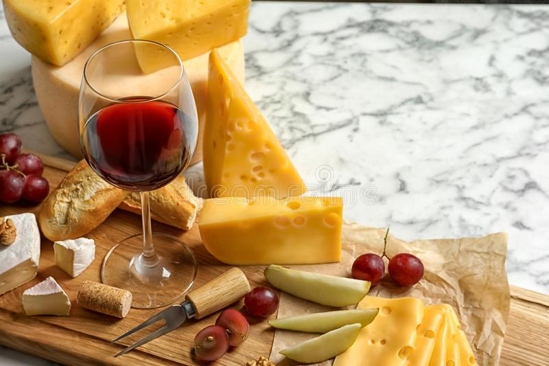 Board with different kinds of delicious cheese, snacks and wine on marble table. Space for text royalty free stock photography