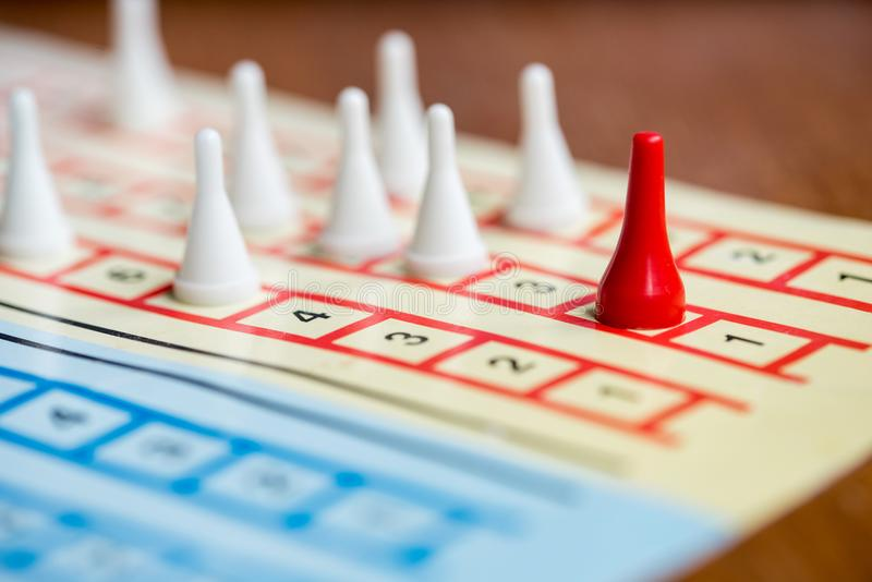 The board game with color pawns, The red chip is in the lead, white competitors. The board game with color pawns, The red chip is in the lead, white competitors stock image