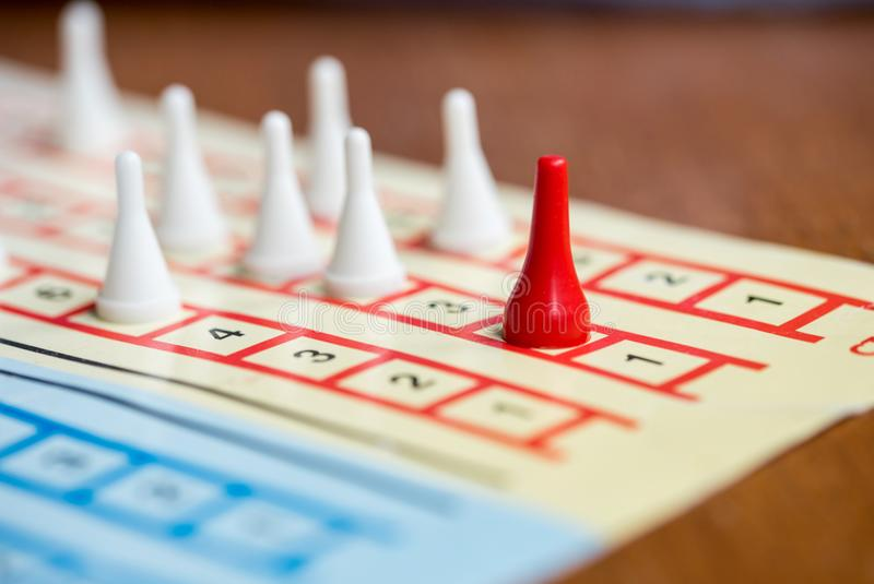 The board game with color pawns, The red chip is in the lead, white competitors. The board game with color pawns, The red chip is in the lead, white competitors stock photos
