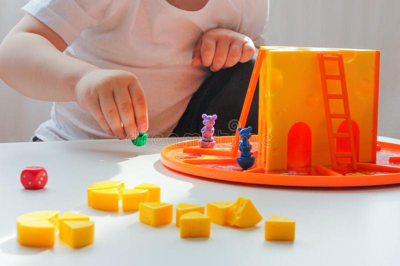 Board game and the concept of children-a LITTLE boy plays a easy game with cheese and mice. royalty free stock photo