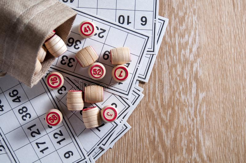 Board game lotto. Cards for the game of lotto on them wooden barrels spilled out of the bag. Wooden background. Group. Entertainment, family vacation. Vintage royalty free stock image