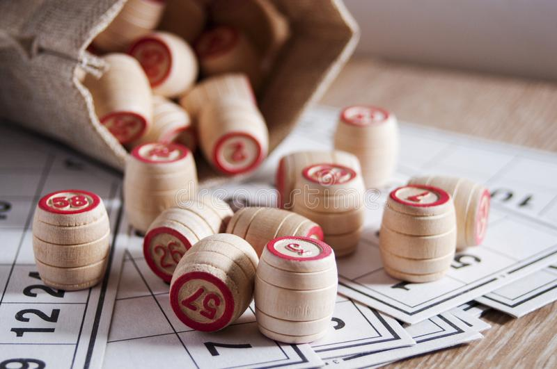 Board game lotto. Cards for the game of lotto on them wooden barrels spilled out of the bag. Wooden background. Group. Entertainment, family vacation. Vintage stock photos