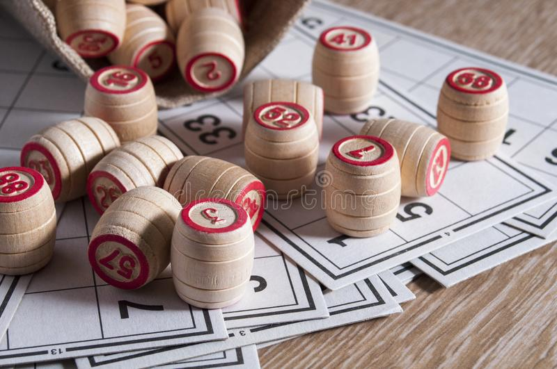 Board game lotto. Cards for the game of lotto on them wooden barrels spilled out of the bag. Wooden background. Group. Entertainment, family vacation. Vintage stock images