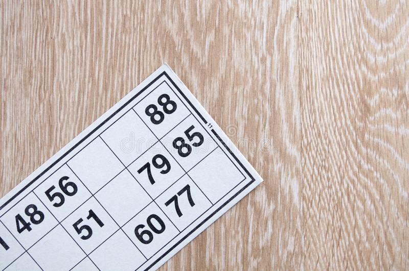 Board game lotto. One game cards for a game lotto. Wooden background. Group entertainment, family leisure. Vintage game. Excitement and good luck. Top view royalty free stock photos