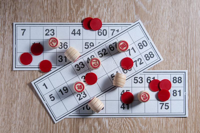 Board game lotto. Wooden lotto barrels, red chips and three game cards for a game in lotto. Wooden background. Group entertainment. Family leisure. Vintage stock photography