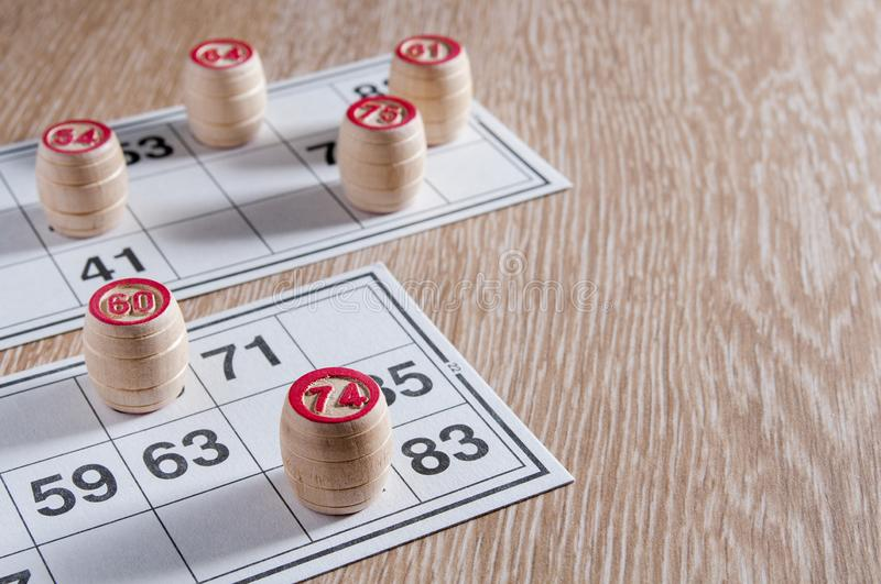 Board game lotto. Wooden lotto barrels and two game cards for a game in lotto. Wooden background. Group entertainment, family. Leisure. Vintage game stock photography