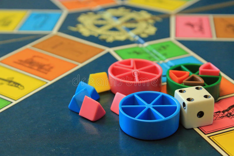 Board games, pieces and dice on game board with lot of colors royalty free stock photos