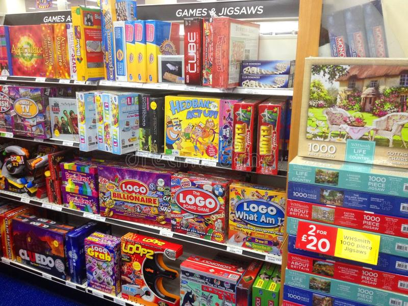 Board games and puzzles in boxes for sale. Various board games and jigsaw puzzles in boxes on shelves in a shop or store for sale royalty free stock photo