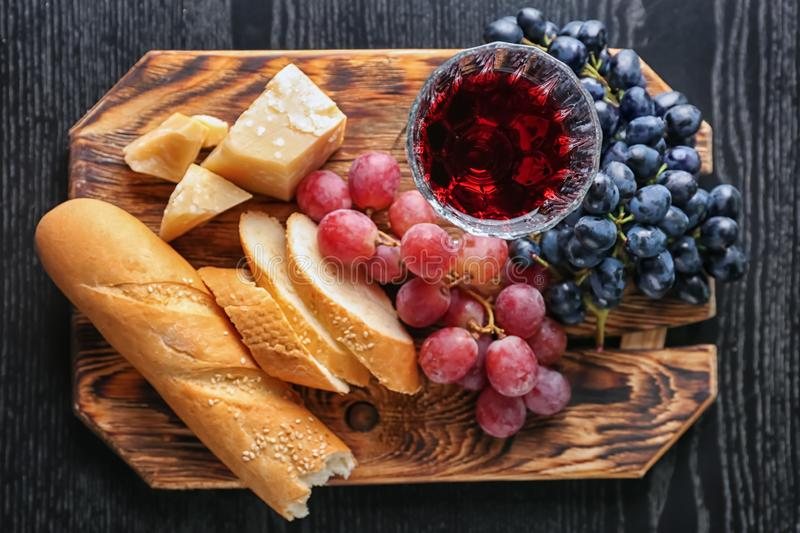 Board with grapes, glass of wine, bread and cheese on dark wooden table royalty free stock images