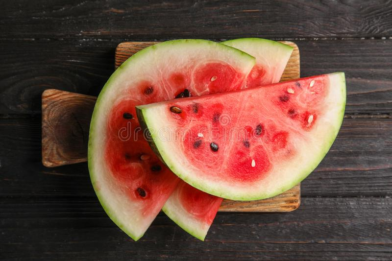 Board with juicy watermelon slices. On wooden background, top view royalty free stock photography