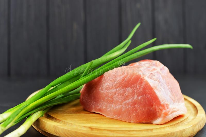 Board meal meat raw pork and beef on a wooden board with green onion. Vegetables diet vitamins on a dark background royalty free stock photo