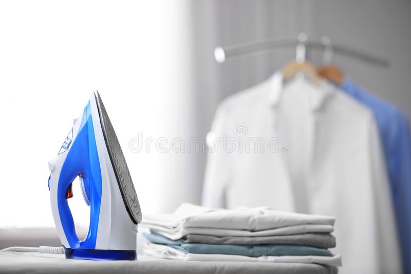 Board with modern iron and stack of clothes, space for text. Laundry day. Board with modern iron and stack of clothes indoors, space for text. Laundry day stock images