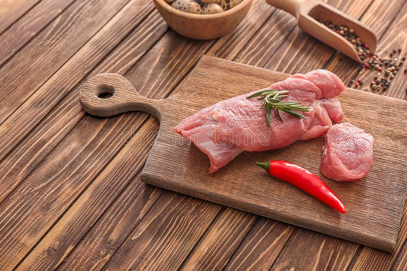 Board with raw pork tenderloin on kitchen table. Fresh meat products stock photos