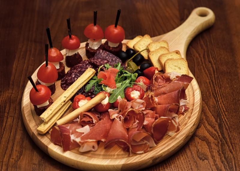 Board with snacks on wooden table. Cold appetizers with tomatoes, sausage, salami, ham, arugula, olives and bread stock images