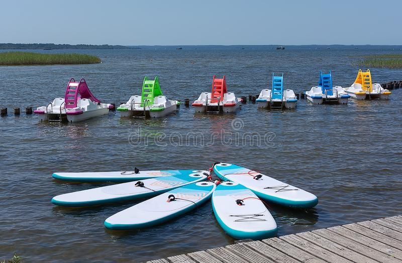 Board For Stand Up Paddle Surfing Sup and Colorful pedal boats with water slides on the water surface of the lake. stock image
