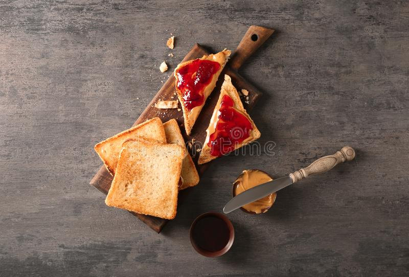 Board with sweet toasted sandwiches and peanut butter on table royalty free stock image