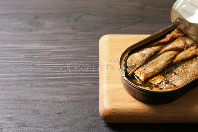 Board with tin can of sprats on wooden table. Space for text. Board with tin can of sprats on wooden table, closeup. Space for text royalty free stock photo