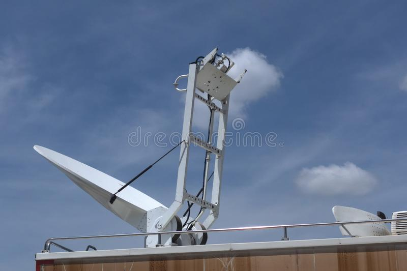 A boardcast white satellite mobile car with blue sky. Background royalty free stock image