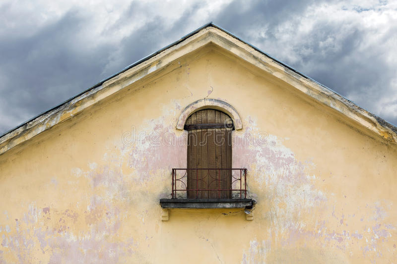 boarded up balcony on weathered plaster wall of gable with peeling paint stock image