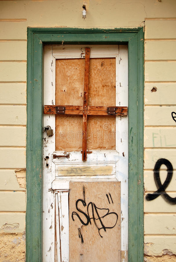 Boarded up door. And weathered wall surface of an abandoned house royalty free stock photo