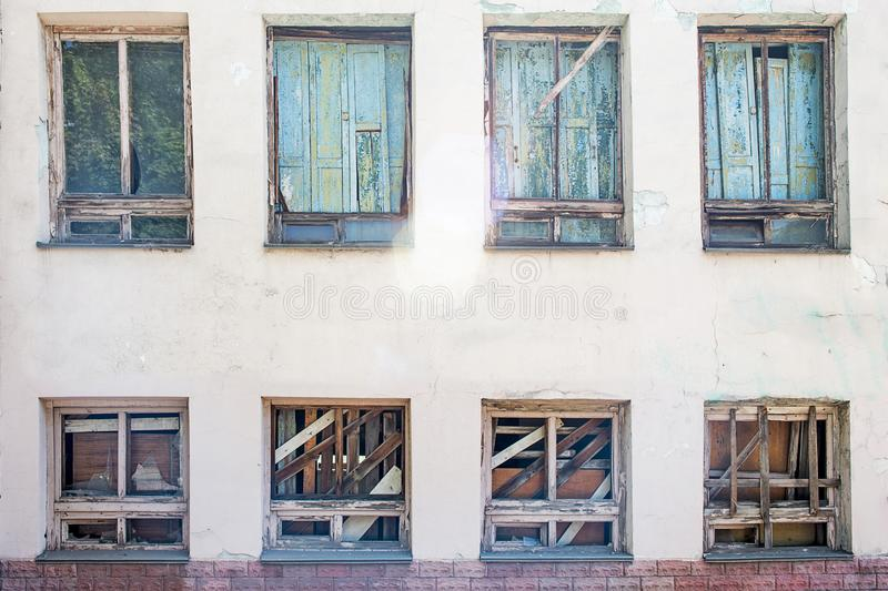 Boarded-up window in an abandoned old building. Broken windows on the wall royalty free stock photos