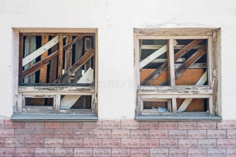 Boarded-up window in an abandoned old building. Broken windows on the wall royalty free stock photography