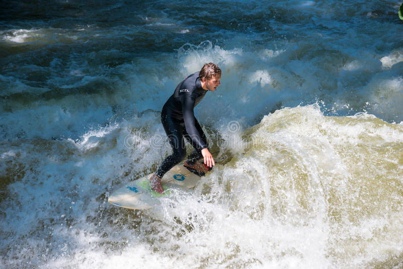 Boarders surfing on the Isar river in Munich, Bayern, Germany. Munich, Germany - June 7, 2016: Boarders surfing on the Isar river in Munich, Bayern, Germany stock photo