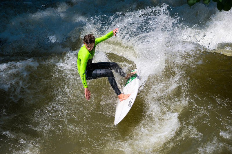 Boarders surfing on the Isar river in Munich, Bayern, Germany. Munich, Germany - June 7, 2016: Boarders surfing on the Isar river in Munich, Bayern, Germany royalty free stock images