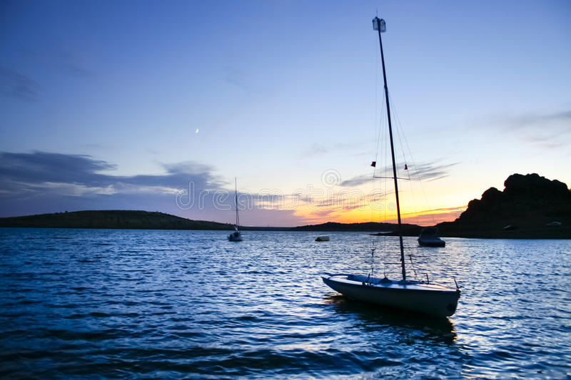 Boarding pontoons of Alange Reservoir, Spain. Sailboats beside the shore of Alange Reservoir at dusk, Extremadura, Spain royalty free stock photos