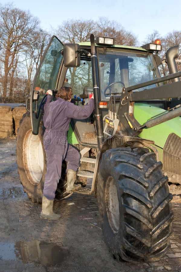 Boarding a tractor. Farm hand boarding a big tractor royalty free stock photography