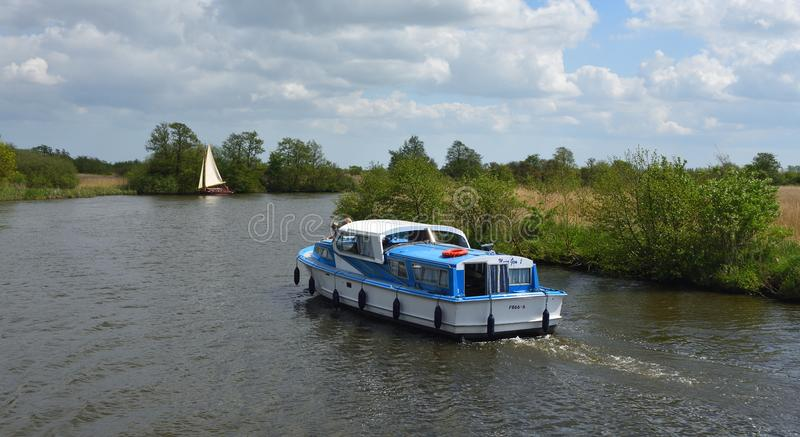 Boards Cruiser and Yacht under sail navigating the river Bure near Horning, the Norfolk Broads. stock photography