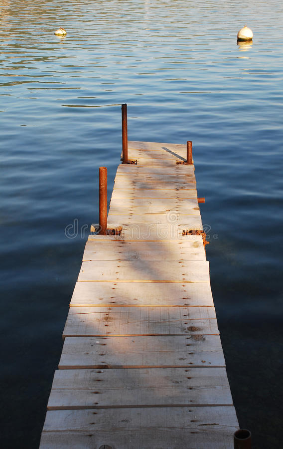 Boardwalk in Bakar Harbour. An old wooden boardwalk juts out into the waters in the bay at Bakar in western croatia royalty free stock images