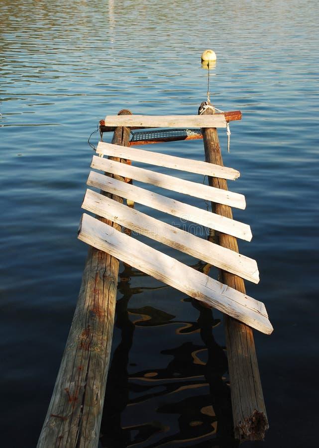 Boardwalk in Bakar Harbour. An old wooden boardwalk juts out into the waters in the bay at Bakar in western croatia stock photo